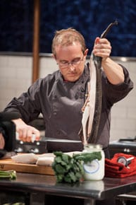 Chef Phillip quickly fillets a whole fish during Round 2 on Food Network's Chopped.